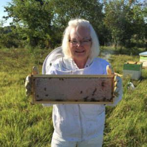 Gina Morrison shows off a frame of capped honey ready to harvest