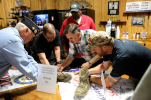 Veterans surround former Marine Tom Fordyce as he signs the flag Ken carries with him