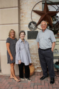 Mary Lee Woodward Nichols, Mary Laura Gibbs, and Mac Woodward stand by Gibbs Brothers & Company Historical Marker