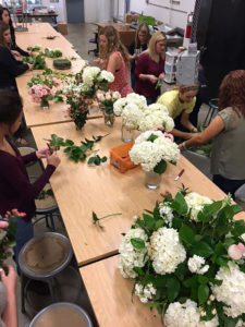MHS students separate wedding florals by type to reassemble into arrangements for residents at a local assisted living home